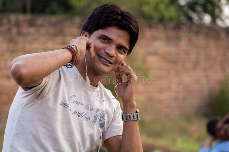 Νεαρός άνδρας που απολαμβάνει τη μουσική με το ακουστικό στοκ φωτογραφία