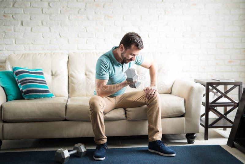 Νεαρός άνδρας που ασκεί με ένα ζευγάρι των αλτήρων στοκ φωτογραφία με δικαίωμα ελεύθερης χρήσης