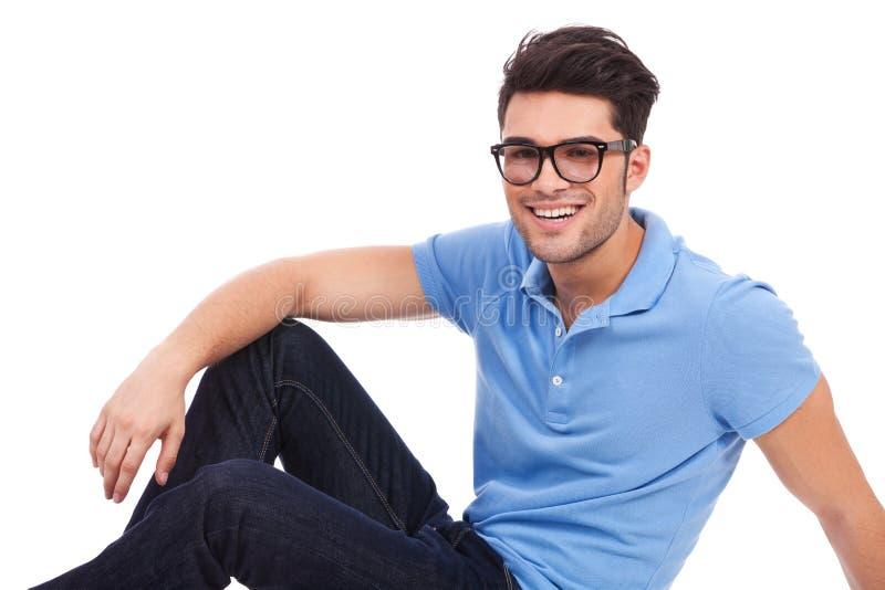 Νεαρός άνδρας που βάζει στο πάτωμα και το χαμόγελο στοκ φωτογραφίες με δικαίωμα ελεύθερης χρήσης