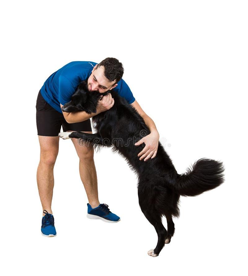 Νεαρός άνδρας που δίνει ένα αγκάλιασμα στο υπάκουο καλό σκυλί κόλλεϊ συνόρων του που απομονώνεται πέρα από το άσπρο υπόβαθρο Φιλί στοκ φωτογραφία με δικαίωμα ελεύθερης χρήσης