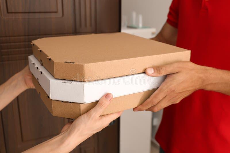 Νεαρός άνδρας που δίνει τα κιβώτια πιτσών στη γυναίκα στην πόρτα Υπηρεσία παράδοσης τροφίμων στοκ εικόνες με δικαίωμα ελεύθερης χρήσης