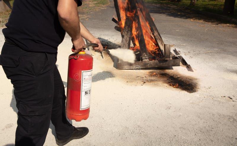 Νεαρός άνδρας που δείχνει έναν πυροσβεστήρα τύπων σκονών προς τα εμπρός στοκ φωτογραφία με δικαίωμα ελεύθερης χρήσης