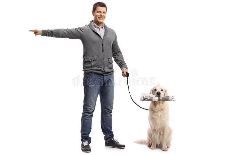 Νεαρός άνδρας που δείχνει με τα WI του χεριών και retriever του Λαμπραντόρ σκυλιών στοκ φωτογραφίες