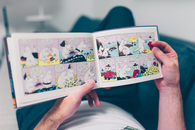 Νεαρός άνδρας που διαβάζει ένα βιβλίο Moomin στοκ εικόνες με δικαίωμα ελεύθερης χρήσης