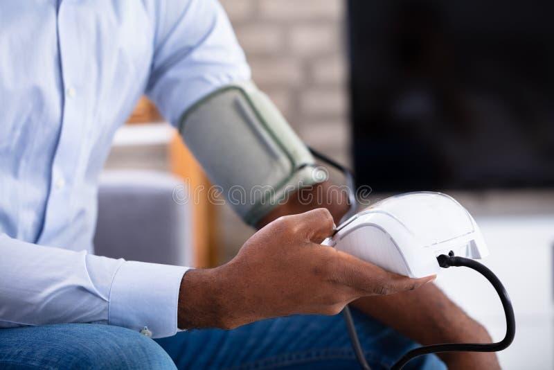 Νεαρός άνδρας που ελέγχει τη πίεση του αίματος του στοκ φωτογραφία με δικαίωμα ελεύθερης χρήσης