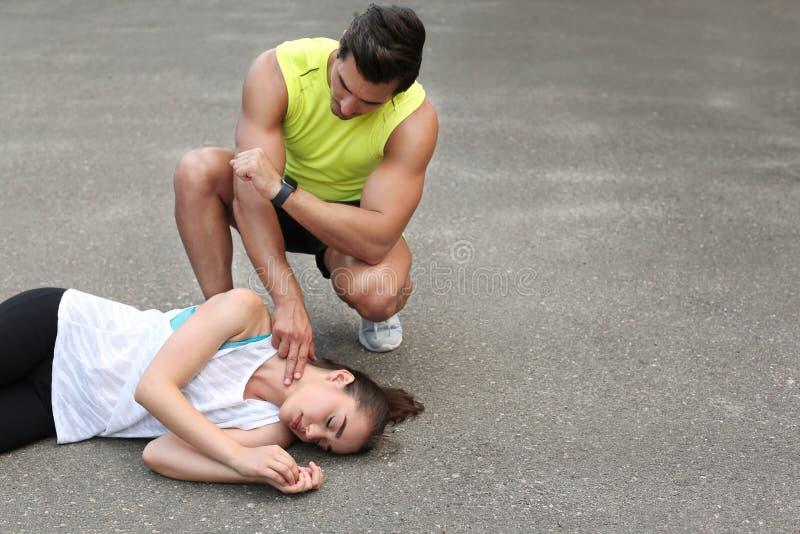 Νεαρός άνδρας που ελέγχει το σφυγμό ασυναίσθητου στην οδό στοκ εικόνα