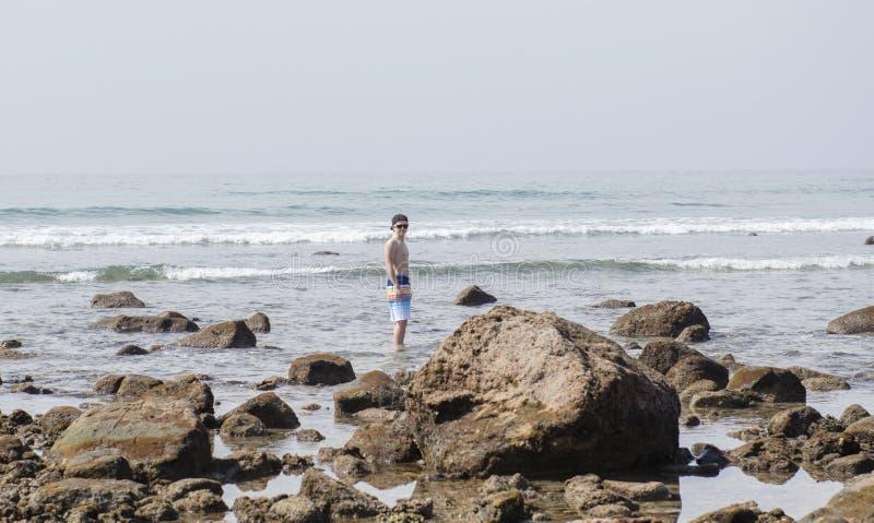 Νεαρός άνδρας που εξερευνά τους βράχους at Low Tide στο Μεξικό στοκ εικόνες