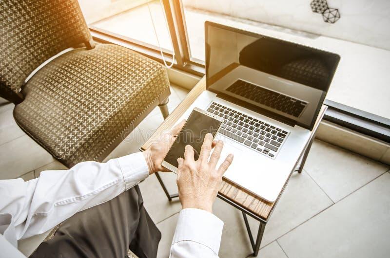 Νεαρός άνδρας που εργάζεται από τη καφετερία που χρησιμοποιεί το έξυπνα τηλέφωνο και το σημειωματάριο στοκ εικόνες