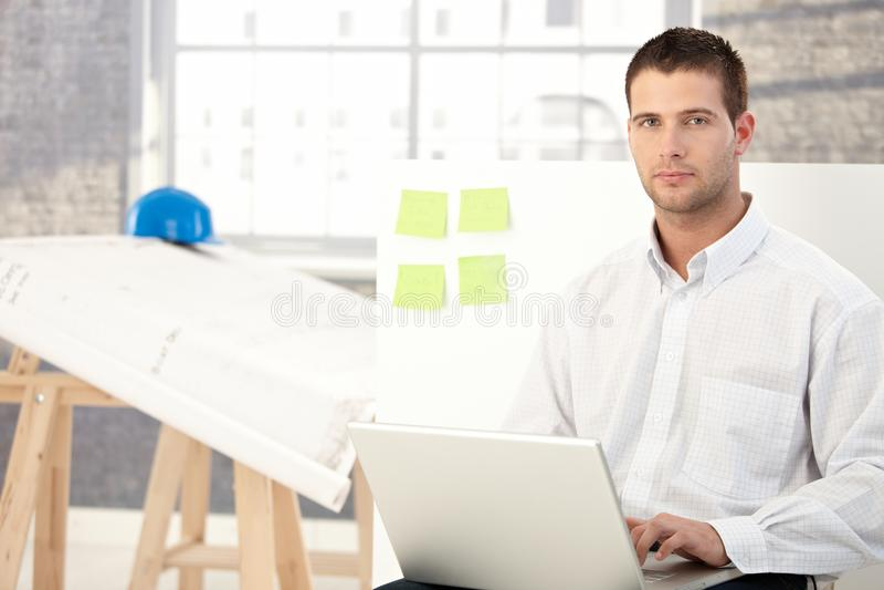 Νεαρός άνδρας που εργάζεται στο γραφείο εφαρμοσμένης μηχανικής στοκ φωτογραφία με δικαίωμα ελεύθερης χρήσης
