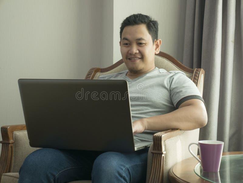 Νεαρός άνδρας που εργάζεται στο σπίτι στο lap-top του, έκφραση χαμόγελου στοκ εικόνα