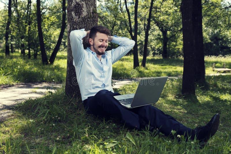 Νεαρός άνδρας που εργάζεται στο lap-top του σε ένα δημόσια πάρκο και ένα χαμόγελο στοκ εικόνες με δικαίωμα ελεύθερης χρήσης