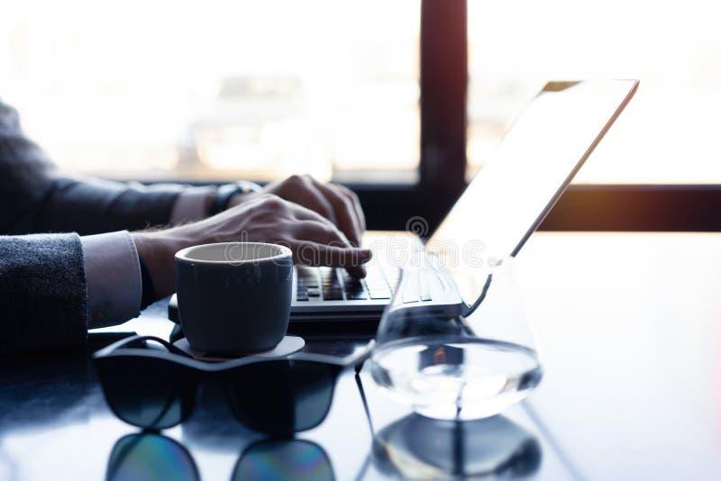 Νεαρός άνδρας που εργάζεται στο lap-top του σε μια καφετερία, οπισθοσκόπο του πολυάσχολου χρησιμοποιώντας lap-top χεριών επιχειρη στοκ φωτογραφία με δικαίωμα ελεύθερης χρήσης