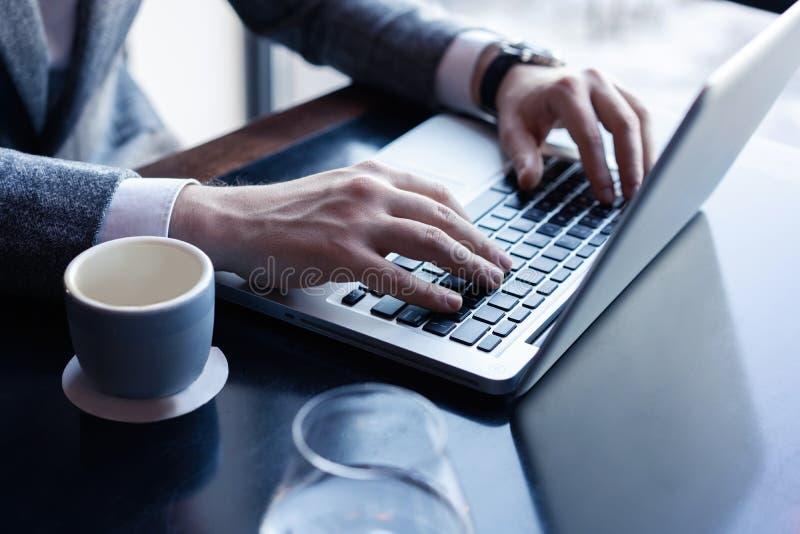 Νεαρός άνδρας που εργάζεται στο lap-top του σε μια καφετερία, οπισθοσκόπο του πολυάσχολου χρησιμοποιώντας lap-top χεριών επιχειρη στοκ φωτογραφίες