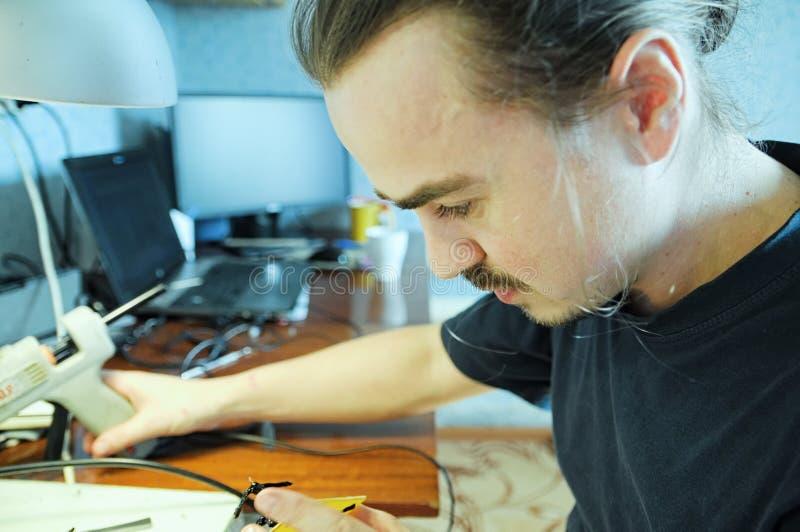 Νεαρός άνδρας που η χειροποίητη μέλισσα παιχνιδιών από την πλαστική κόλλα, χόμπι χειροτεχνίας διακοσμήσεων σπιτιών, διαδικασία δη στοκ φωτογραφία