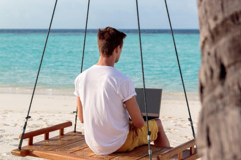 Νεαρός άνδρας που κάθεται σε μια ταλάντευση και εργασία με το lap-top του Σαφές μπλε τροπικό νερό ως υπόβαθρο στοκ φωτογραφία με δικαίωμα ελεύθερης χρήσης