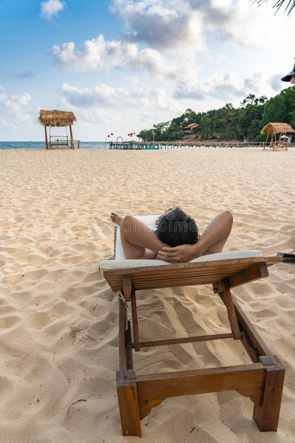 Νεαρός άνδρας που κάνει ηλιοθεραπεία στην άσπρη παραλία άμμου στοκ εικόνες