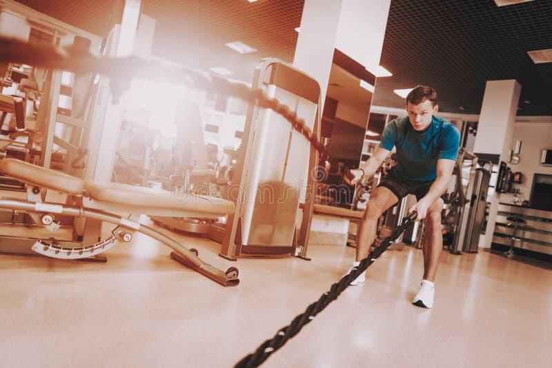 Νεαρός άνδρας που κάνει τις ασκήσεις με το σχοινί στην αθλητική λέσχη στοκ φωτογραφία