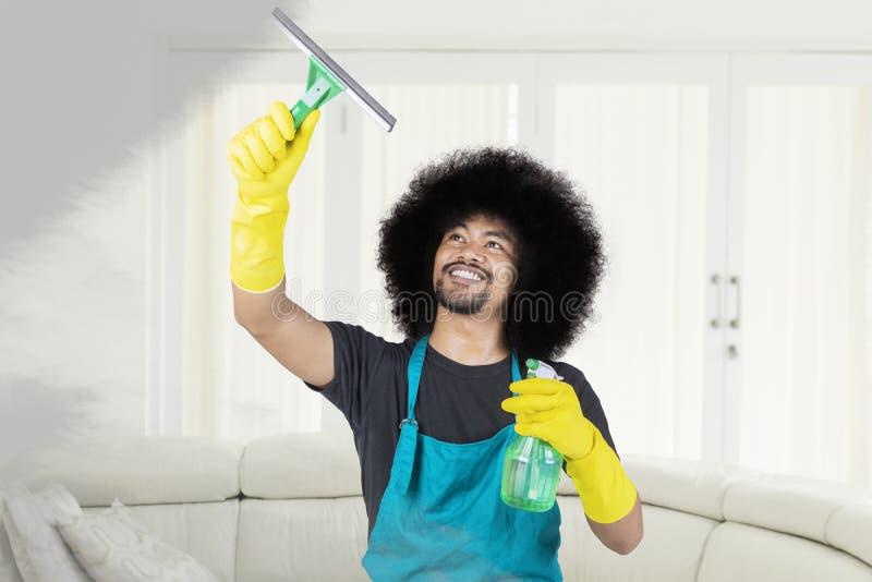 Νεαρός άνδρας που καθαρίζει έναν σκονισμένο καθρέφτη στο σπίτι στοκ φωτογραφία με δικαίωμα ελεύθερης χρήσης