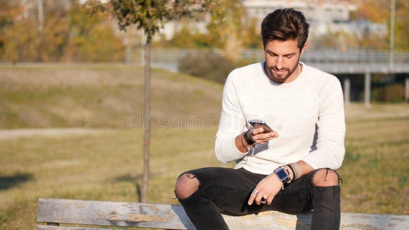 Νεαρός άνδρας που καθιστά το τηλεφώνημα υπαίθριο στην πόλη στοκ φωτογραφία με δικαίωμα ελεύθερης χρήσης