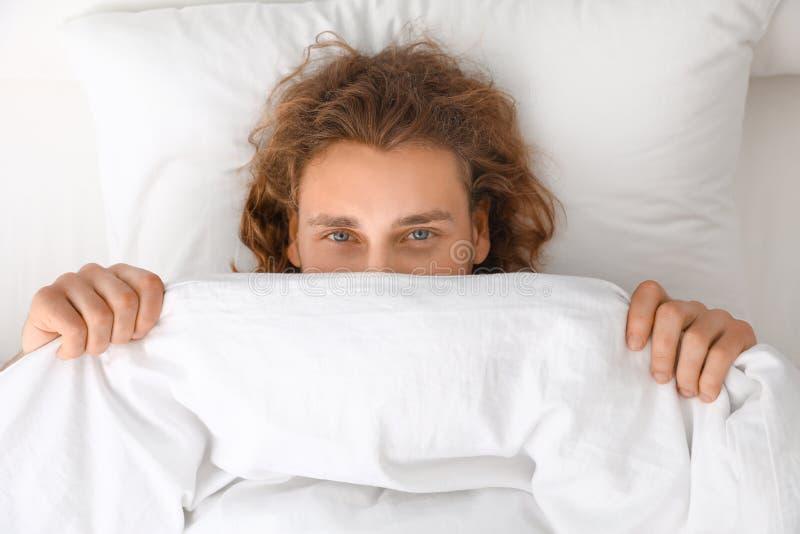 Νεαρός άνδρας που καλύπτει το πρόσωπό του με το κάλυμμα στο μαξιλάρι Ώρα για ύπνο στοκ εικόνες με δικαίωμα ελεύθερης χρήσης
