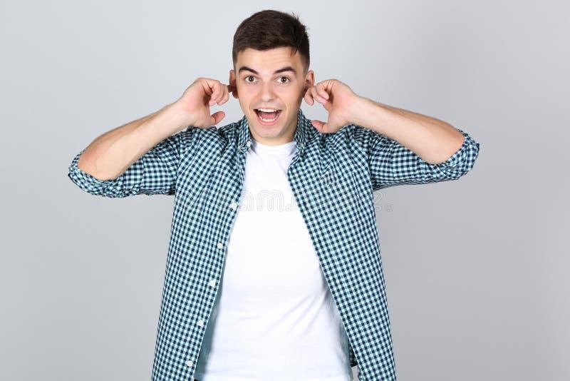 Νεαρός άνδρας που κλείνει τα αυτιά με τα δάχτυλα στοκ εικόνα με δικαίωμα ελεύθερης χρήσης
