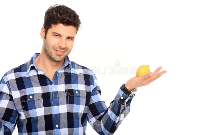 Νεαρός άνδρας που κρατά ένα λεμόνι στοκ φωτογραφία