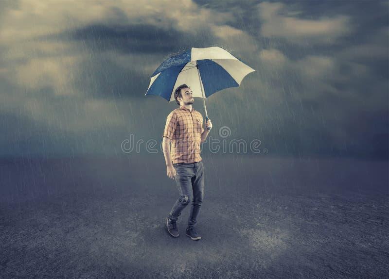 Νεαρός άνδρας που κρατά μια ομπρέλα στοκ εικόνα με δικαίωμα ελεύθερης χρήσης