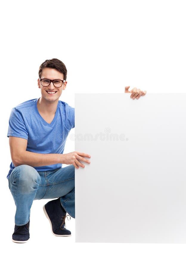Νεαρός άνδρας που κρατά την κενή αφίσα στοκ εικόνα με δικαίωμα ελεύθερης χρήσης