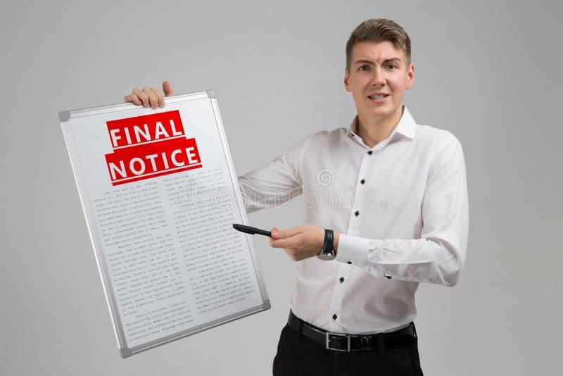 Νεαρός άνδρας που κρατά την τελική ειδοποίηση απομονωμένη στο ελαφρύ υπόβαθρο στοκ εικόνα