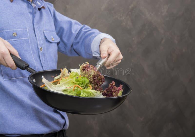 Νεαρός άνδρας που μαγειρεύει τα υγιή τρόφιμα στην κουζίνα στοκ εικόνες