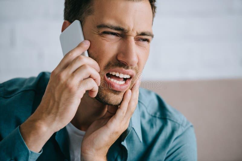νεαρός άνδρας που μιλά από το smartphone και που κοιτάζει μακριά πάσχοντας από τον πόνο δοντιών στο σπίτι στοκ φωτογραφία
