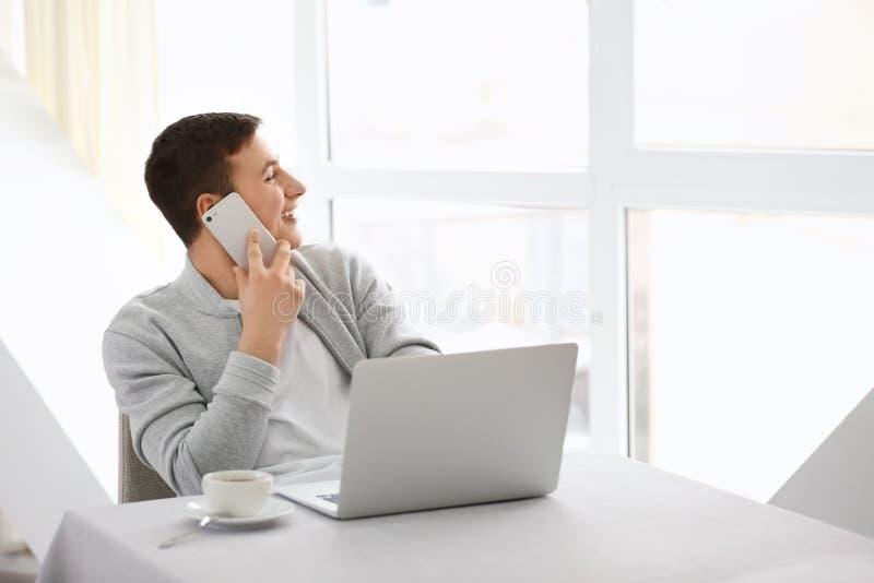 Νεαρός άνδρας που μιλά στο τηλέφωνο εργαζόμενος με το lap-top στον καφέ στοκ εικόνες