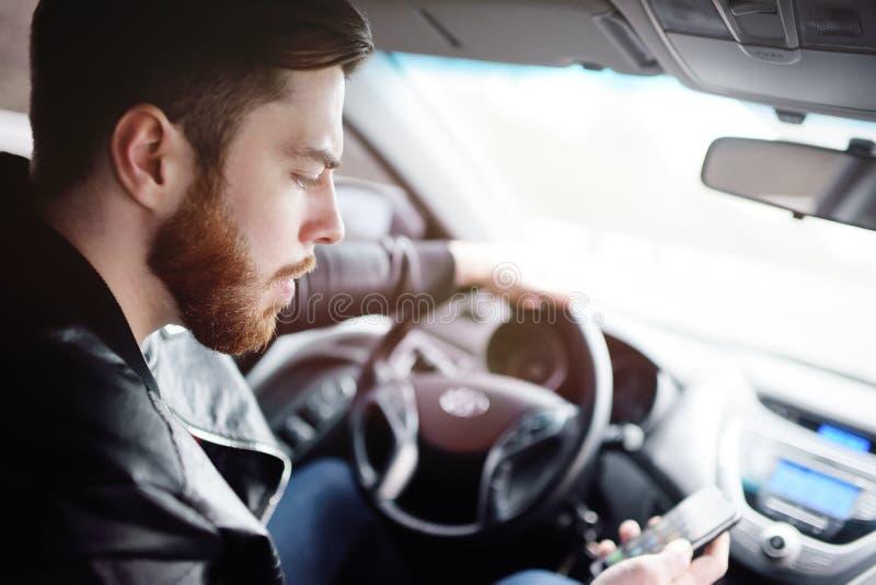Νεαρός άνδρας που μιλά στο τηλέφωνο οδηγώντας ένα αυτοκίνητο στοκ φωτογραφία με δικαίωμα ελεύθερης χρήσης