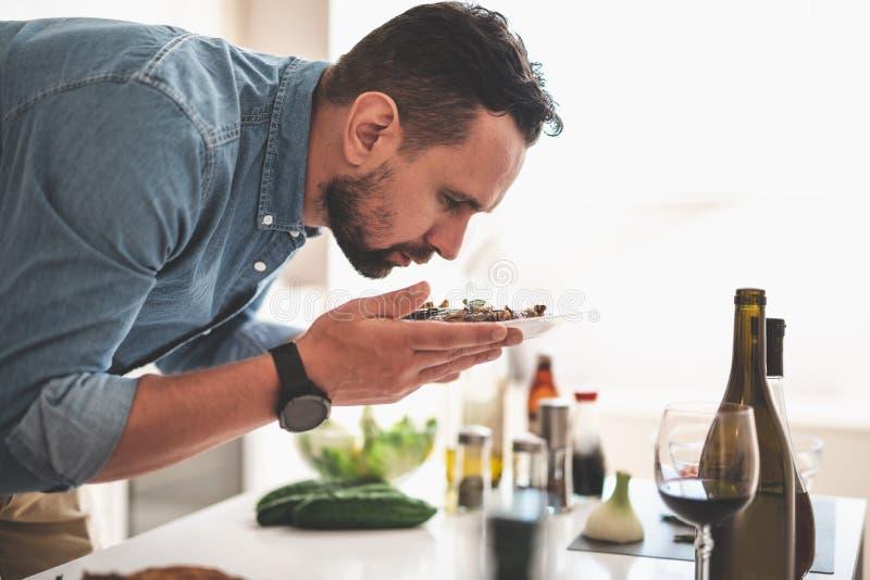 Νεαρός άνδρας που μυρίζει το θαυμάσιο άρωμα της ψημένης μπριζόλας βόειου κρέατος στοκ εικόνα