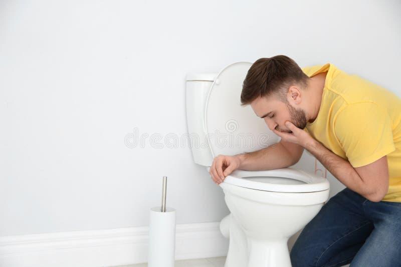 Νεαρός άνδρας που πάσχει από τη ναυτία πέρα από το κύπελλο τουαλετών στοκ φωτογραφία