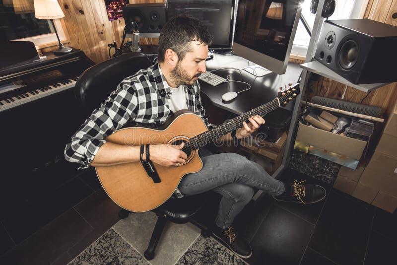 Νεαρός άνδρας που παίζει την κλασσική κιθάρα στο στούντιο Κιθαρίστας μουσικών στοκ φωτογραφία