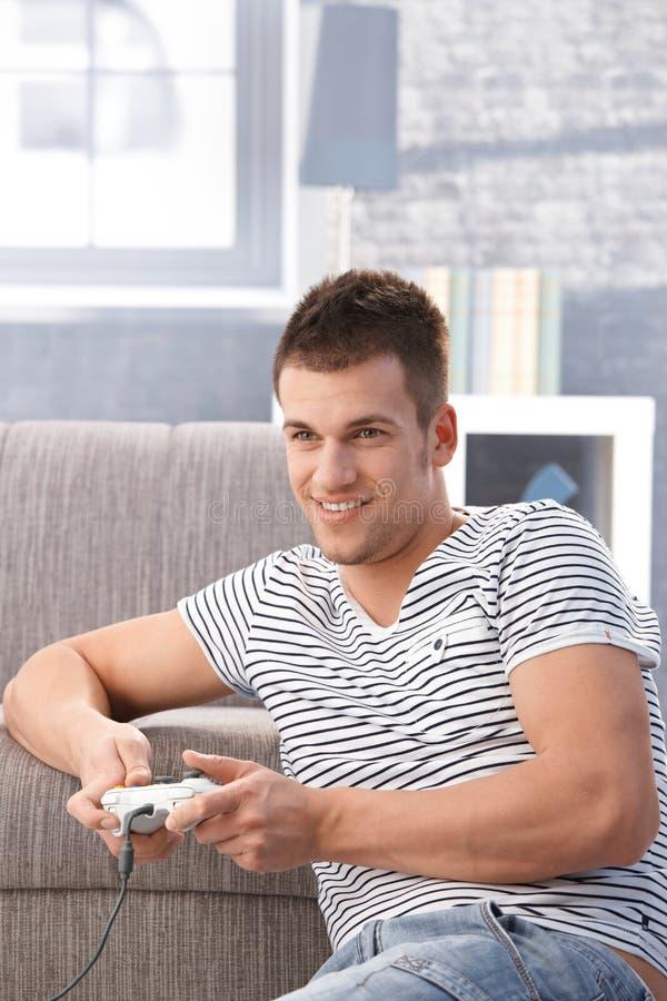 Νεαρός άνδρας που παίζει το τηλεοπτικό παιχνίδι στο σπίτι στοκ εικόνα με δικαίωμα ελεύθερης χρήσης