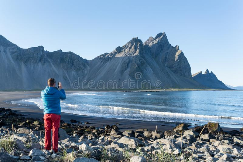 Νεαρός άνδρας που παίρνει μια φωτογραφία στο βουνό Vestrahorn στη χερσόνησο Stokksnes, Ισλανδία στοκ φωτογραφία με δικαίωμα ελεύθερης χρήσης