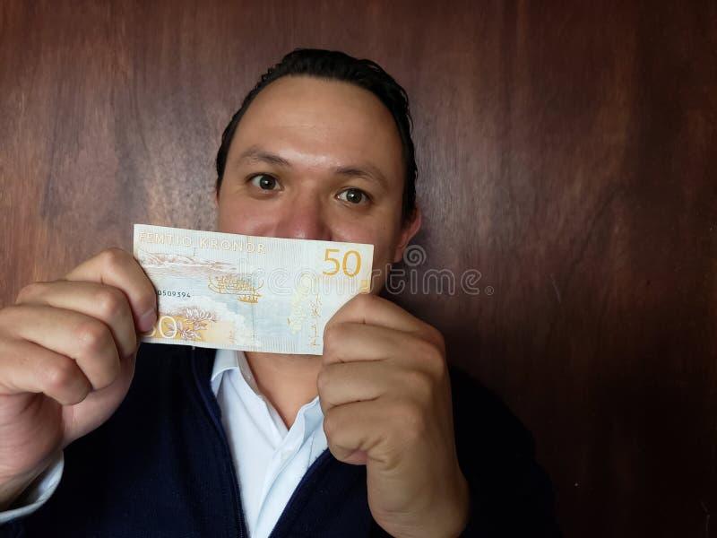 νεαρός άνδρας που παρουσιάζει και που κρατά σουηδικό τραπεζογραμμάτιο του kronor πενήντα στοκ εικόνα με δικαίωμα ελεύθερης χρήσης