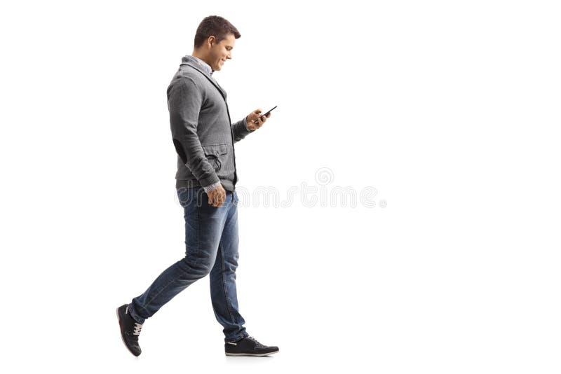 Νεαρός άνδρας που περπατά και που χρησιμοποιεί ένα τηλέφωνο στοκ φωτογραφία