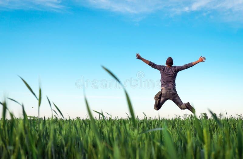 Νεαρός άνδρας που πηδά για τη χαρά πέρα από έναν πράσινο τομέα σίτου Όμορφος αγρότης Γεωργία άνοιξη Το άτομο θαυμάζει την ομορφιά στοκ εικόνα
