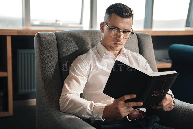 Νεαρός άνδρας που πιστεύει στη μοίρα που διαβάζει τη Βίβλο στο Σαββατοκύριακο στοκ φωτογραφίες με δικαίωμα ελεύθερης χρήσης