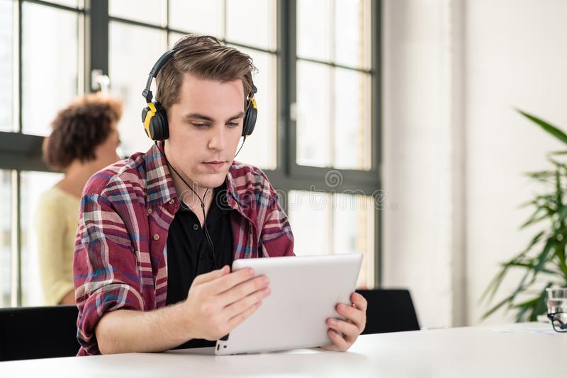 Νεαρός άνδρας που προσέχει ένα βίντεο στο PC ταμπλετών στην εργασία στοκ φωτογραφίες