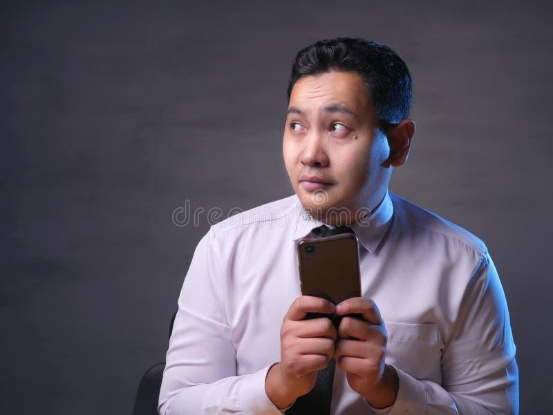 Νεαρός άνδρας που σκέφτεται κουβεντιάζοντας στο έξυπνο τηλέφωνο στοκ εικόνα με δικαίωμα ελεύθερης χρήσης