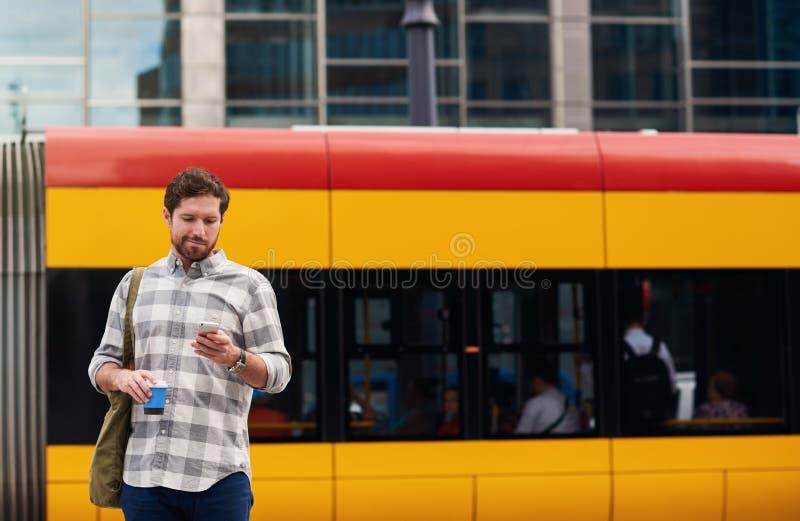 Νεαρός άνδρας που στέκεται σε μια στάση λεωφορείου που χρησιμοποιεί το κινητό τηλέφωνο του στοκ εικόνες