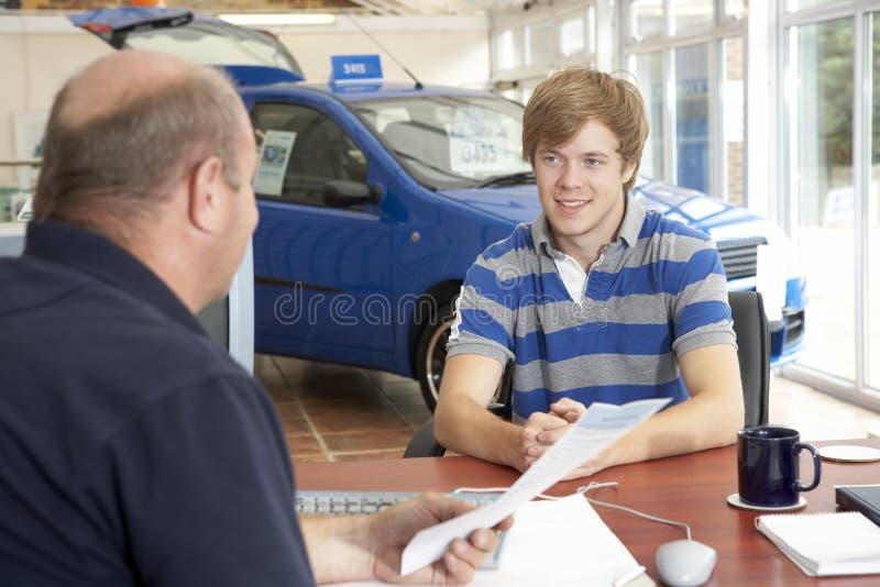 Νεαρός άνδρας που συμπληρώνει τη γραφική εργασία στην αίθουσα εκθέσεως αυτοκινήτων στοκ φωτογραφία με δικαίωμα ελεύθερης χρήσης
