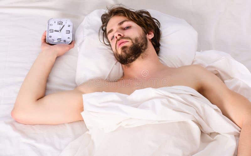 Νεαρός άνδρας που τεντώνει ξυπνώντας το πρωί Ο εύθυμος νεαρός άνδρας ξυπνά μετά από να κοιμηθεί το πρωί στοκ εικόνες