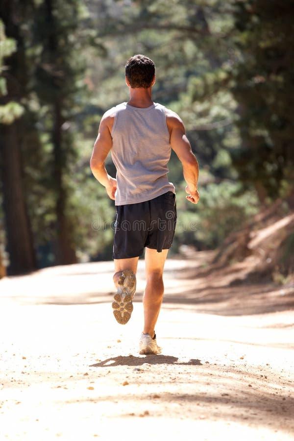 Νεαρός άνδρας που τρέχει κατά μήκος της παρόδου χωρών στοκ φωτογραφία με δικαίωμα ελεύθερης χρήσης