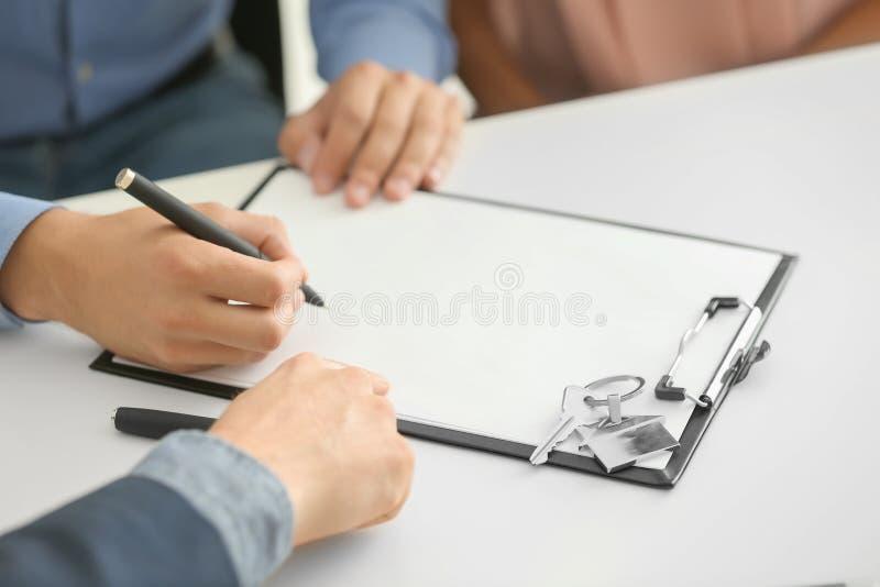 Νεαρός άνδρας που υπογράφει μια σύμβαση για την αγορά του σπιτιού στην αρχή του κτηματομεσίτη στοκ φωτογραφία