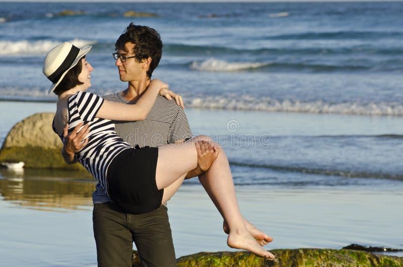 Νεαρός άνδρας που φέρνει την όμορφη γυναίκα στην παραλία στοκ εικόνα με δικαίωμα ελεύθερης χρήσης